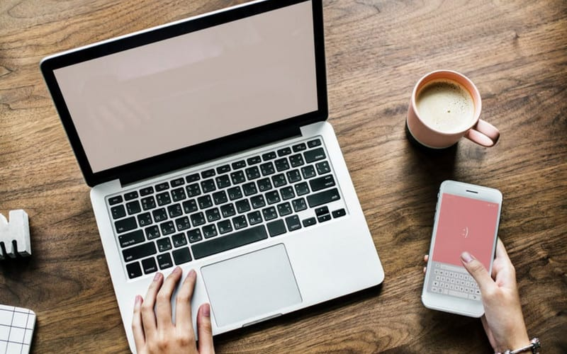 laptop on desk with pink mobile screen_blog_content_planner